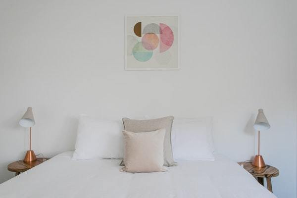 Cama hecha con sábanas blancas