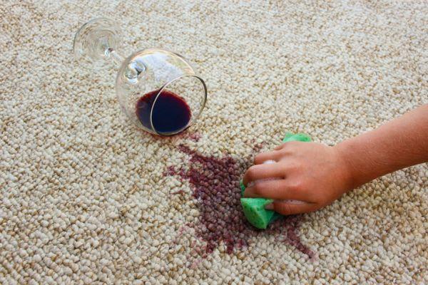 Mano limpiando vino derramado