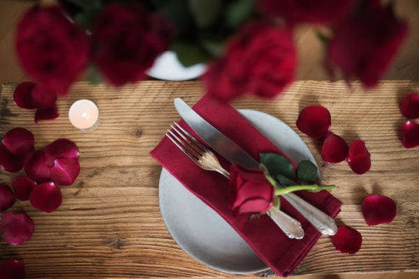 Decoracion para la mesa de la cena de san valentin con petalos de rosa