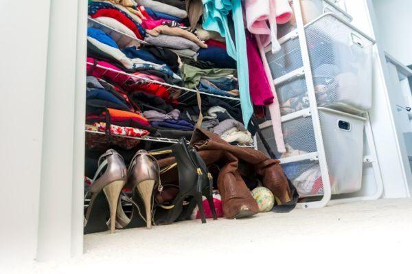 como-organizar-un-vestidor-pequeno-ropa-amontonada-istock